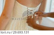Купить «Woman trying on wedding dress with the assistance of fashion designer», видеоролик № 29693131, снято 23 августа 2016 г. (c) Wavebreak Media / Фотобанк Лори