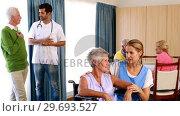 Купить «Doctor and nurse interacting with senior citizens», видеоролик № 29693527, снято 27 апреля 2016 г. (c) Wavebreak Media / Фотобанк Лори
