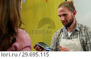 Купить «Woman paying bill through credit card», видеоролик № 29695115, снято 4 октября 2016 г. (c) Wavebreak Media / Фотобанк Лори
