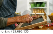 Купить «Male staff writing on slate in organic section», видеоролик № 29695135, снято 4 октября 2016 г. (c) Wavebreak Media / Фотобанк Лори