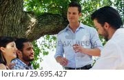 Купить «Group of friends interacting with each other while having lunch», видеоролик № 29695427, снято 21 ноября 2016 г. (c) Wavebreak Media / Фотобанк Лори
