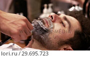 Купить «Man getting his beard shaved with razor in barber shop», видеоролик № 29695723, снято 19 сентября 2016 г. (c) Wavebreak Media / Фотобанк Лори