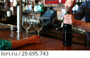Купить «Barman opening wine bottle with corkscrew at bar counter», видеоролик № 29695743, снято 14 ноября 2016 г. (c) Wavebreak Media / Фотобанк Лори