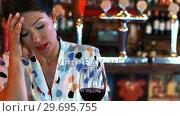 Купить «Sad woman having red wine», видеоролик № 29695755, снято 14 ноября 2016 г. (c) Wavebreak Media / Фотобанк Лори