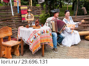 Купить «Russia, Khabarovsk, August 18, 2018: a man and a woman in Russian-national costumes play the accordion and balalaika», фото № 29696131, снято 18 августа 2018 г. (c) Катерина Белякина / Фотобанк Лори