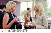 Купить «Female business executives interacting with each other while having coffee», видеоролик № 29696279, снято 3 ноября 2016 г. (c) Wavebreak Media / Фотобанк Лори