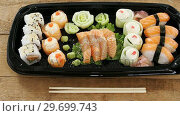 Купить «Sushi rolls with salmon in plastic tray», видеоролик № 29699743, снято 8 декабря 2016 г. (c) Wavebreak Media / Фотобанк Лори