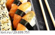 Купить «Plastic tray of various sushi rolls with salmon», видеоролик № 29699751, снято 8 декабря 2016 г. (c) Wavebreak Media / Фотобанк Лори