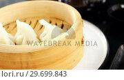 Купить «Steamed dumplings in bamboo steamer», видеоролик № 29699843, снято 8 декабря 2016 г. (c) Wavebreak Media / Фотобанк Лори