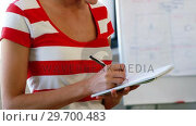 Купить «Female executive writing on spiral notepad», видеоролик № 29700483, снято 31 января 2016 г. (c) Wavebreak Media / Фотобанк Лори