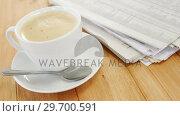 Купить «Coffee and newspaper on wooden plank», видеоролик № 29700591, снято 6 октября 2016 г. (c) Wavebreak Media / Фотобанк Лори