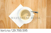 Купить «Overhead view of white coffee cup with creamy froth», видеоролик № 29700595, снято 6 октября 2016 г. (c) Wavebreak Media / Фотобанк Лори