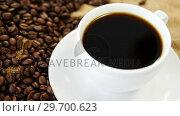 Купить «Coffee cup and roasted beans on sack textile», видеоролик № 29700623, снято 6 октября 2016 г. (c) Wavebreak Media / Фотобанк Лори