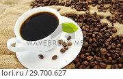 Купить «Black coffee, coffee beans and leaf on sack», видеоролик № 29700627, снято 6 октября 2016 г. (c) Wavebreak Media / Фотобанк Лори