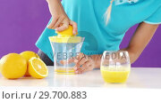 Woman preparing sweet lime juice from juicer against violet background. Стоковое видео, агентство Wavebreak Media / Фотобанк Лори