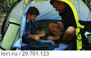 Купить «Father and son playing cards in the tent», видеоролик № 29701123, снято 2 марта 2017 г. (c) Wavebreak Media / Фотобанк Лори