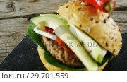 Купить «Hamburger on slate board», видеоролик № 29701559, снято 13 января 2017 г. (c) Wavebreak Media / Фотобанк Лори