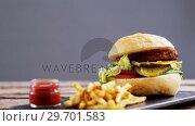 Купить «Hamburger and french fries with ketchup on slate board», видеоролик № 29701583, снято 13 января 2017 г. (c) Wavebreak Media / Фотобанк Лори
