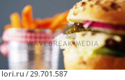 Купить «Hamburger and french fries against grey background», видеоролик № 29701587, снято 13 января 2017 г. (c) Wavebreak Media / Фотобанк Лори