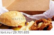 Купить «Hamburger and french fries in a take away container on table», видеоролик № 29701655, снято 13 января 2017 г. (c) Wavebreak Media / Фотобанк Лори