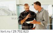 Купить «Happy colleagues discussing over digital tablet», видеоролик № 29702823, снято 26 марта 2017 г. (c) Wavebreak Media / Фотобанк Лори