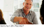 Купить «Business colleagues shaking hands in the office», видеоролик № 29702827, снято 26 марта 2017 г. (c) Wavebreak Media / Фотобанк Лори