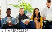 Купить «Business colleagues using electronic devices while sitting on sofa», видеоролик № 29702839, снято 26 марта 2017 г. (c) Wavebreak Media / Фотобанк Лори