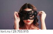 Купить «Portrait of beautiful woman wearing masquerade mask 4k», видеоролик № 29703915, снято 22 мая 2017 г. (c) Wavebreak Media / Фотобанк Лори