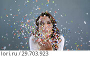 Купить «Smiling woman blowing confetti 4k», видеоролик № 29703923, снято 22 мая 2017 г. (c) Wavebreak Media / Фотобанк Лори