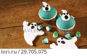 Купить «Halloween cupcakes and gingerbread cookies on a wooden table 4k», видеоролик № 29705075, снято 26 мая 2017 г. (c) Wavebreak Media / Фотобанк Лори