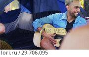 Купить «Man playing guitar for his friends at a music festival 4k», видеоролик № 29706095, снято 9 марта 2017 г. (c) Wavebreak Media / Фотобанк Лори