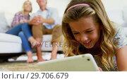 Купить «Daughter using digital tablet in living room while parents sitting on sofa 4k», видеоролик № 29706679, снято 24 марта 2017 г. (c) Wavebreak Media / Фотобанк Лори