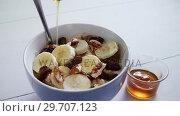 Купить «Honey pouring into a fruit cereal bowl 4k», видеоролик № 29707123, снято 13 июня 2017 г. (c) Wavebreak Media / Фотобанк Лори