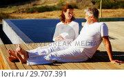 Купить «Happy couple relaxing on wooden plank 4k», видеоролик № 29707391, снято 12 мая 2017 г. (c) Wavebreak Media / Фотобанк Лори