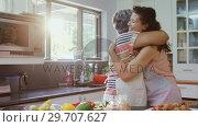 Купить «Mother and daughter embracing each other in kitchen 4k», видеоролик № 29707627, снято 20 марта 2017 г. (c) Wavebreak Media / Фотобанк Лори