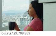 Купить «Woman having cup of coffee in living room 4k», видеоролик № 29708859, снято 25 марта 2017 г. (c) Wavebreak Media / Фотобанк Лори