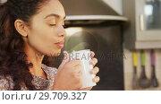 Купить «Woman wearing winter cloths having a coffee in the kitchen 4K 4k», видеоролик № 29709327, снято 31 мая 2017 г. (c) Wavebreak Media / Фотобанк Лори