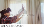Купить «Happy woman sitting on sofa using virtual reality headset 4K 4k», видеоролик № 29709351, снято 31 мая 2017 г. (c) Wavebreak Media / Фотобанк Лори