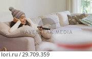 Купить «Happy woman in warm clothing lying on sofa watching television 4K 4k», видеоролик № 29709359, снято 31 мая 2017 г. (c) Wavebreak Media / Фотобанк Лори