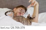 Купить «Happy young man lying on bed playing with his tabby cat 4K 4k», видеоролик № 29709379, снято 31 мая 2017 г. (c) Wavebreak Media / Фотобанк Лори