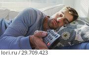 Купить «Young man lying on sofa watching television 4K 4k», видеоролик № 29709423, снято 31 мая 2017 г. (c) Wavebreak Media / Фотобанк Лори