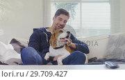 Купить «Smiling man sitting on sofa stroking his pet dog while watching television 4K 4k», видеоролик № 29709427, снято 31 мая 2017 г. (c) Wavebreak Media / Фотобанк Лори
