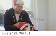 Купить «Smiling young man putting santa cap on his pet dog 4K 4k», видеоролик № 29709431, снято 31 мая 2017 г. (c) Wavebreak Media / Фотобанк Лори