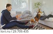 Купить «Smiling young man sitting on ground feeding food to playful pet dog 4K 4k», видеоролик № 29709435, снято 31 мая 2017 г. (c) Wavebreak Media / Фотобанк Лори