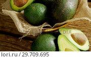 Купить «Avocados in jute fabric placed on wooden table 4K 4k», видеоролик № 29709695, снято 12 июня 2017 г. (c) Wavebreak Media / Фотобанк Лори