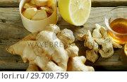 Купить «Herbal tea with ginger and lemon on wooden table 4k», видеоролик № 29709759, снято 12 июня 2017 г. (c) Wavebreak Media / Фотобанк Лори