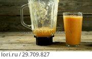 Купить «Glass of a fruit juice with juicer on wooden table 4k», видеоролик № 29709827, снято 12 июня 2017 г. (c) Wavebreak Media / Фотобанк Лори