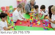 Купить «Happy kids and female teacher playing together with colorful toy building blocks in classroom at elementary school», видеоролик № 29710179, снято 18 декабря 2018 г. (c) Яков Филимонов / Фотобанк Лори
