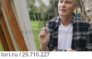Купить «Man painting on canvas in the garden 4k», видеоролик № 29710227, снято 31 августа 2017 г. (c) Wavebreak Media / Фотобанк Лори