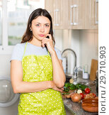 Купить «Young girl housewife in apron looking tired at kitchen», фото № 29710903, снято 18 апреля 2018 г. (c) Яков Филимонов / Фотобанк Лори